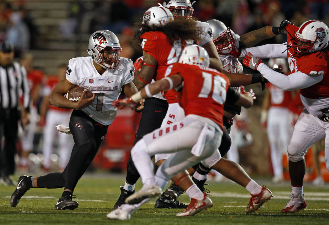 UNLV quarterback Armani Rogers, left, tries to get past the New Mexico defense during the second half of an NCAA college football game in Albuquerque, N.M., Friday, Nov. 17, 2017. (AP Photo/Andres ...