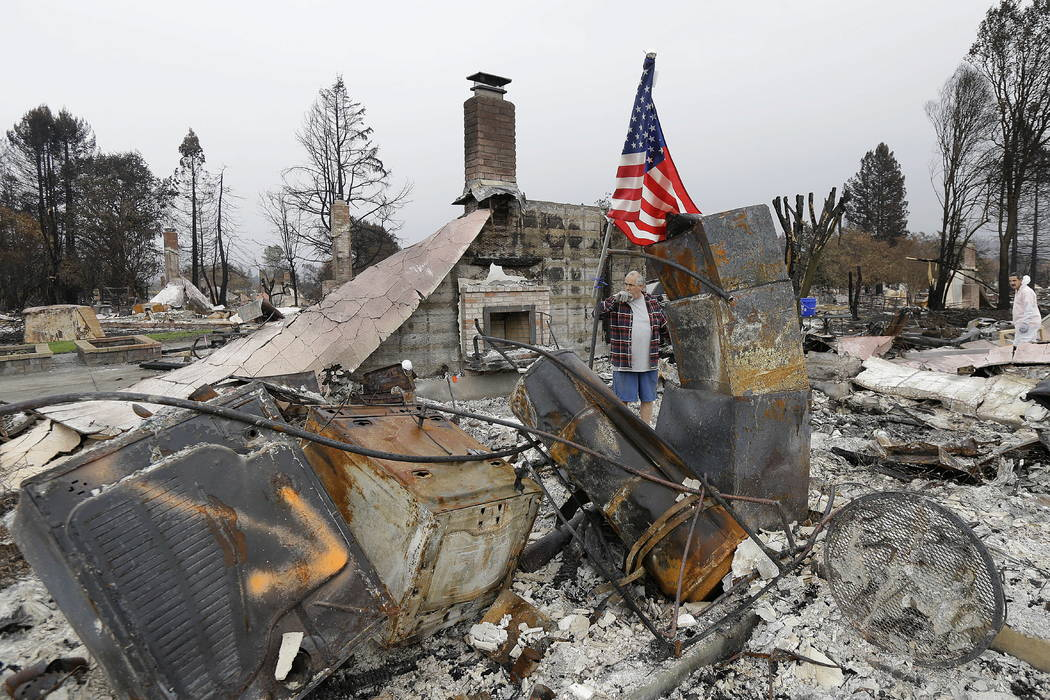 Larry Keyser looks around as he and volunteers from Samaritan's Purse disaster relief sift through remains of his family's home destroyed by fires in the Coffey Park area of Santa Rosa, Calif., We ...
