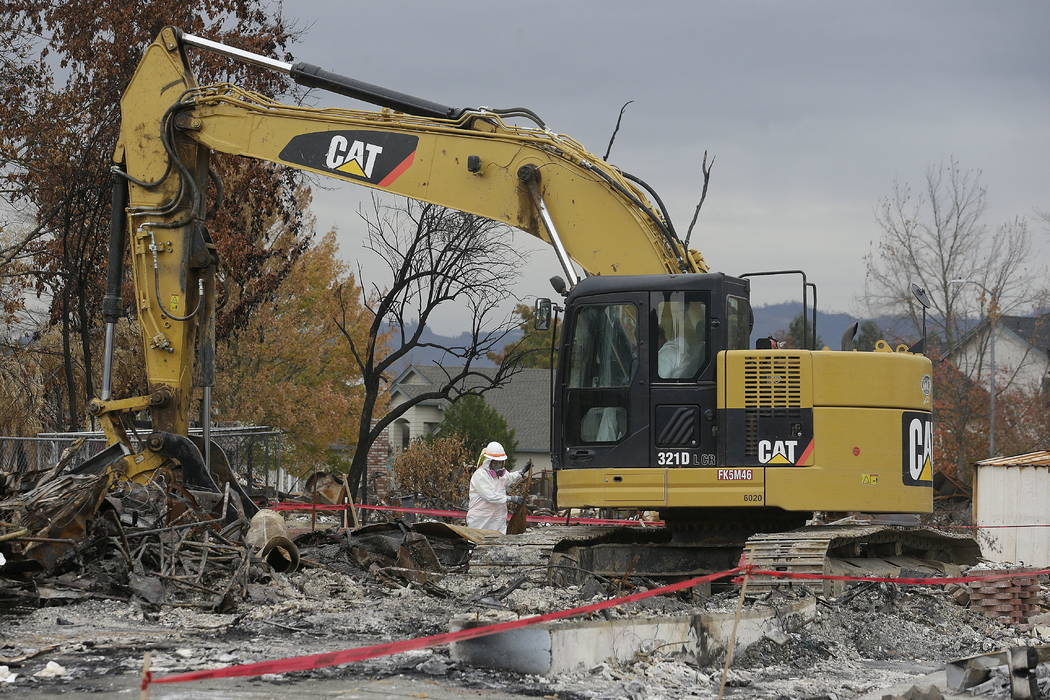 Work crews remove debris a the site of a home destroyed by fires in the Coffey Park area of Santa Rosa, Calif., Wednesday, Nov. 8, 2017.  (AP Photo/Jeff Chiu)