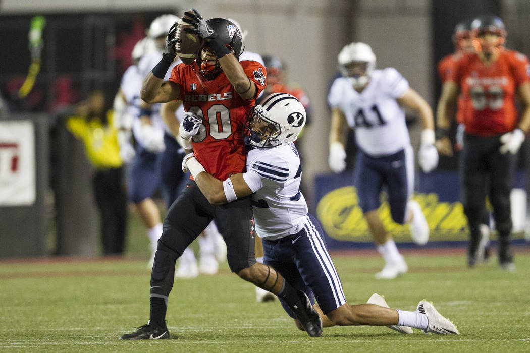 UNLV Rebels wide receiver Brandon Presley (80) is tackled against Brigham Young Cougars defensive back Chris Wilcox (32) after a catch in the football game at Sam Boyd Stadium in Las Vegas, Friday ...