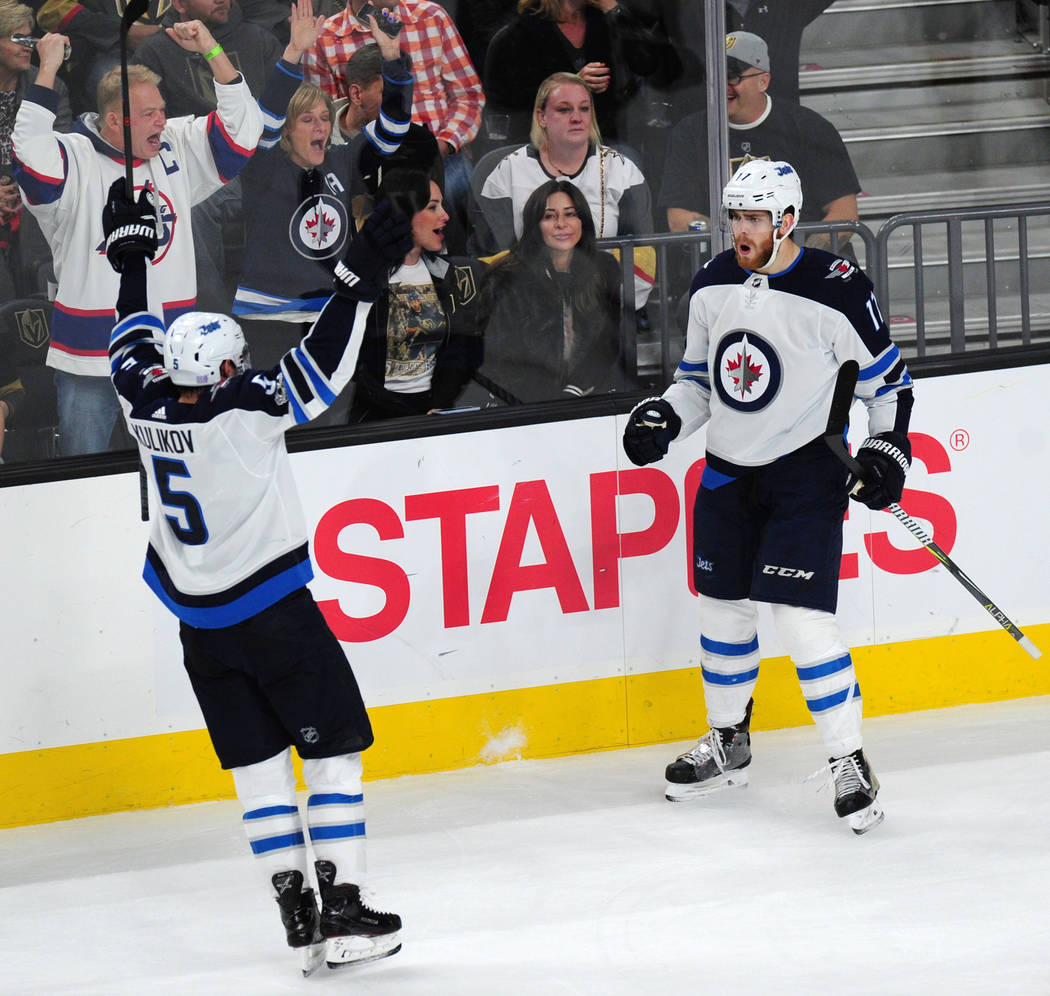Winnipeg Jets center Adam Lowry (17) celebrates a goal against the Vegas Golden Knights with defenseman Dmitry Kulikov (5) in the first period of their NHL hockey game at T-Mobile Arena in Las Veg ...