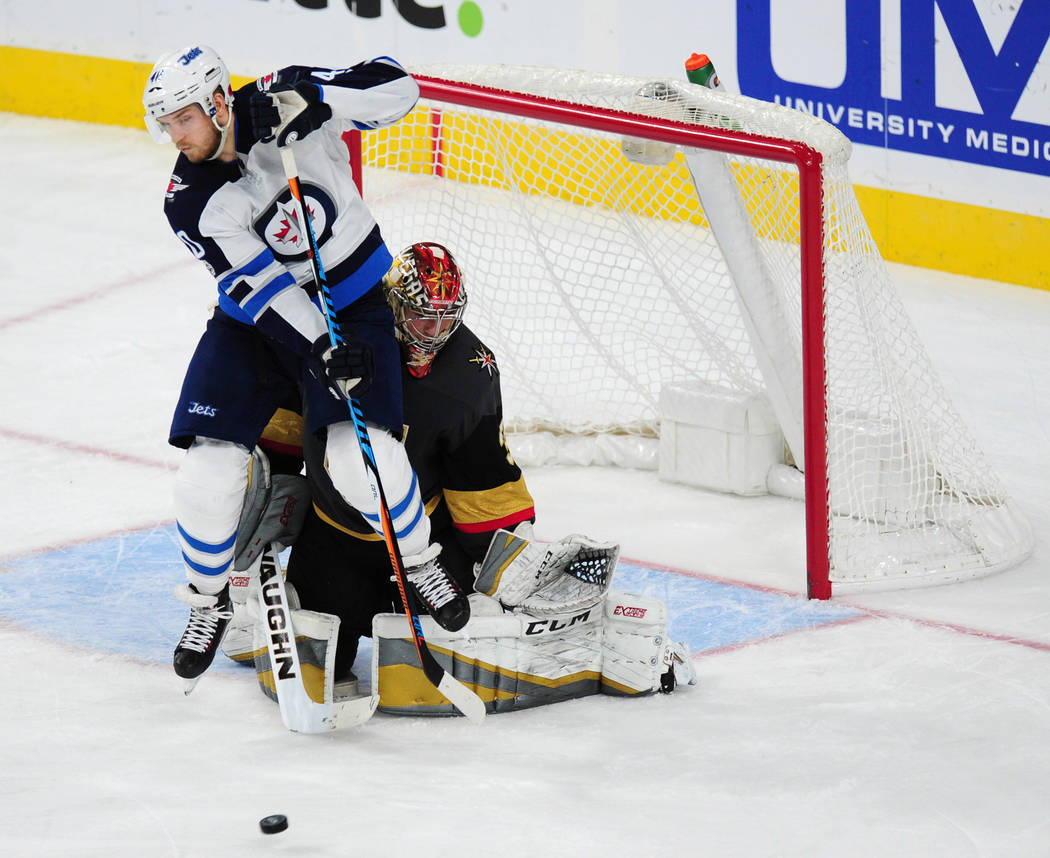Winnipeg Jets forward Joel Armia screens Vegas Golden Knights goalie Maxime Lagace as a shot comes in during the third period of their NHL hockey game at T-Mobile Arena in Las Vegas Friday Novembe ...