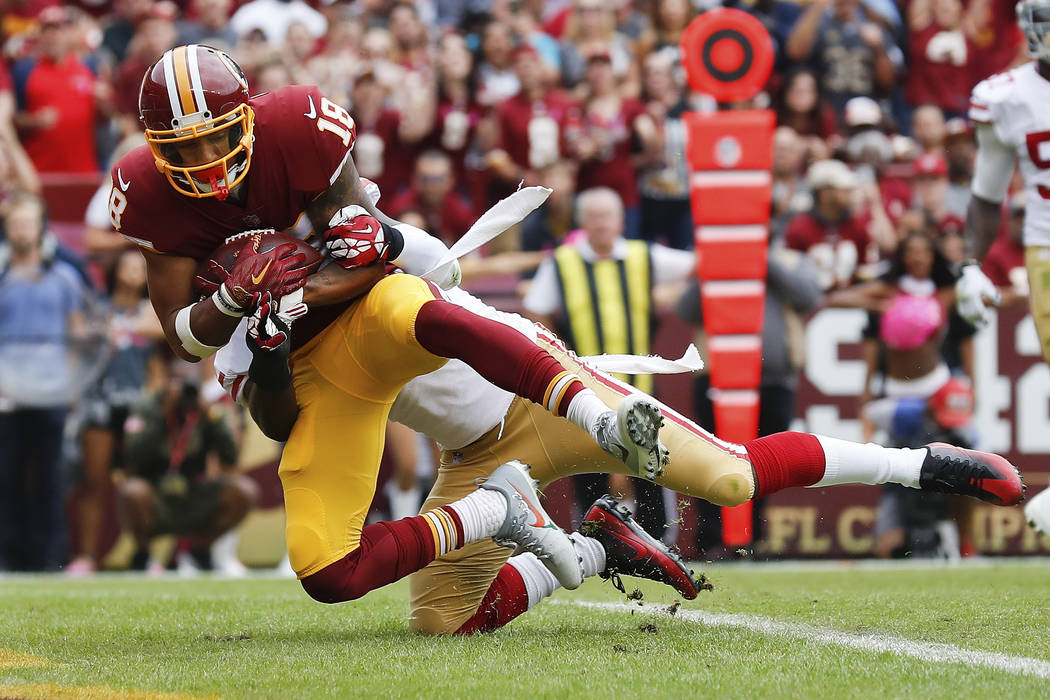 Washington Redskins wide receiver Josh Doctson (18) pulls in a touchdown pass as San Francisco 49ers free safety Jaquiski Tartt (29) pulls him to the turf during the first half of an NFL football  ...