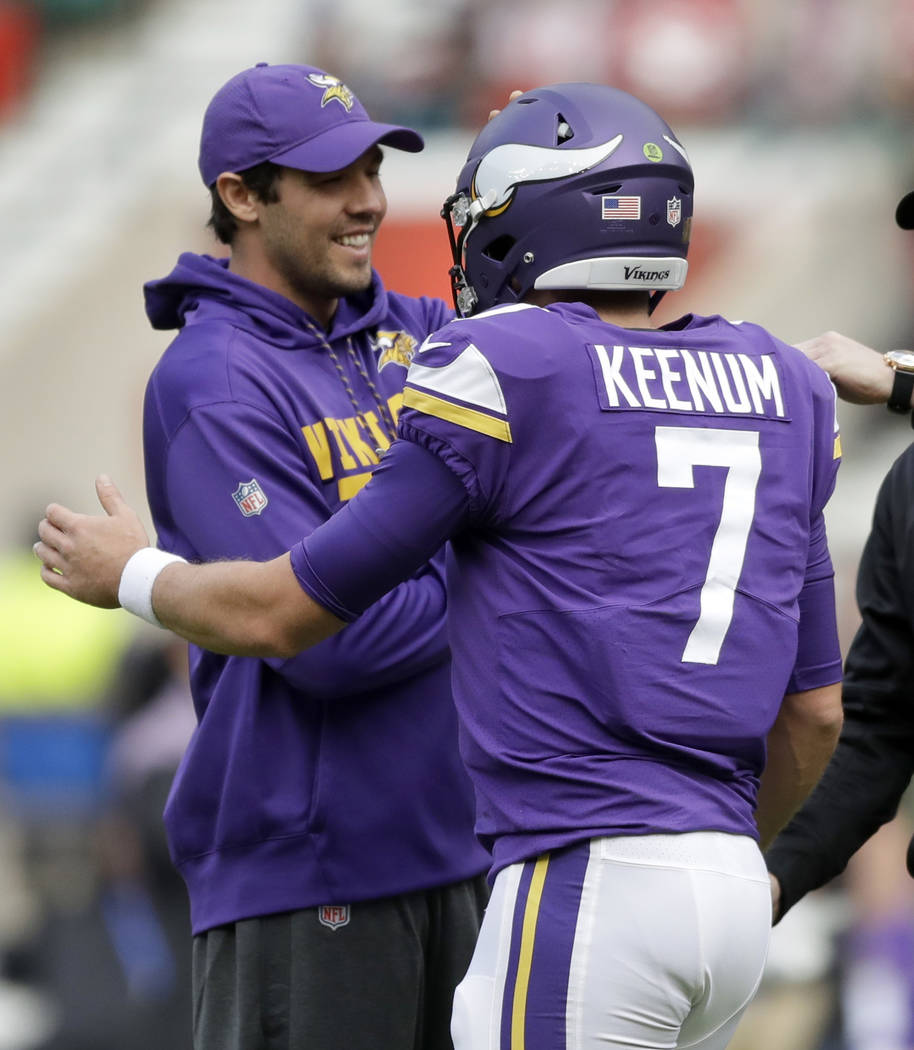 Minnesota Vikings quarterbacks Sam Bradford, left, and Case Keenum (7) greet each other during the warm-up before an NFL football game against Cleveland Browns at Twickenham Stadium in London, Sun ...