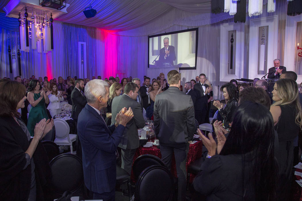 The audience of more than 400 gives a standing ovation to Sheriff Joe Lombardo, Mandalay Bay security guard Jesus Campos and building engineer Stephen Schuck at the 26th annual Camelot gala at Opp ...