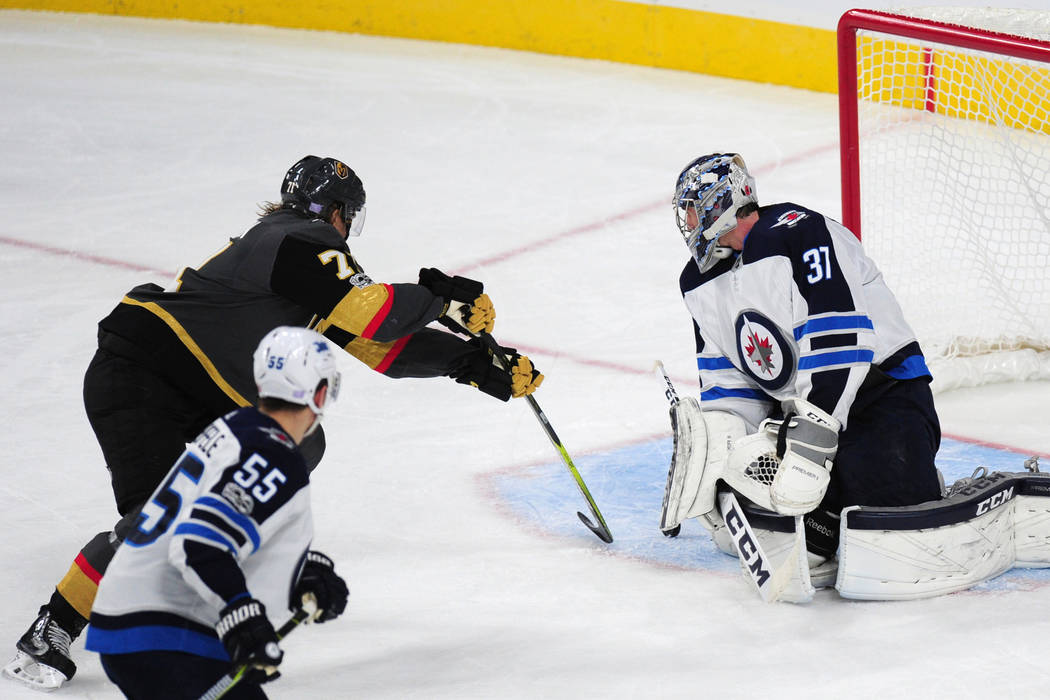 Vegas Golden Knights forward William Karlsson scores a goal off a rebound against Winnipeg Jets goalie Connor Hellebuyck in the second period of their NHL hockey game at T-Mobile Arena in Las Vega ...