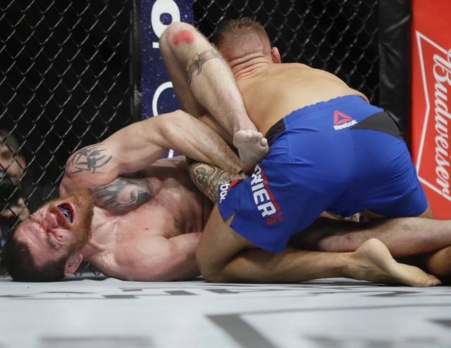 Jim Miller, left, fights Dustin Poirier during a lightweight mixed martial arts bout at UFC 208 on Saturday, Feb. 11, 2017, in New York. Poirier won the fight. (AP Photo/Frank Franklin II)