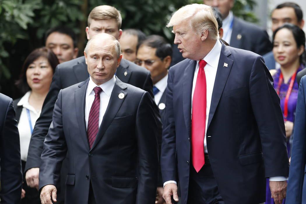 President Donald Trump, right, and Russia's President Vladimir Putin talk during the family photo session at the APEC Summit in Danang, Vietnam Saturday, Nov. 11, 2017. (Jorge Silva/Pool Photo via AP)