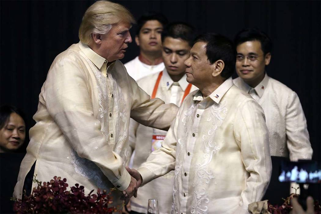President Donald Trump, left, shakes hands with Philippines President Rodrigo Duterte at the ASEAN Summit dinner at the SMX Convention Center, Sunday, Nov. 12, 2017, in Manila, Philippines. Trump  ...