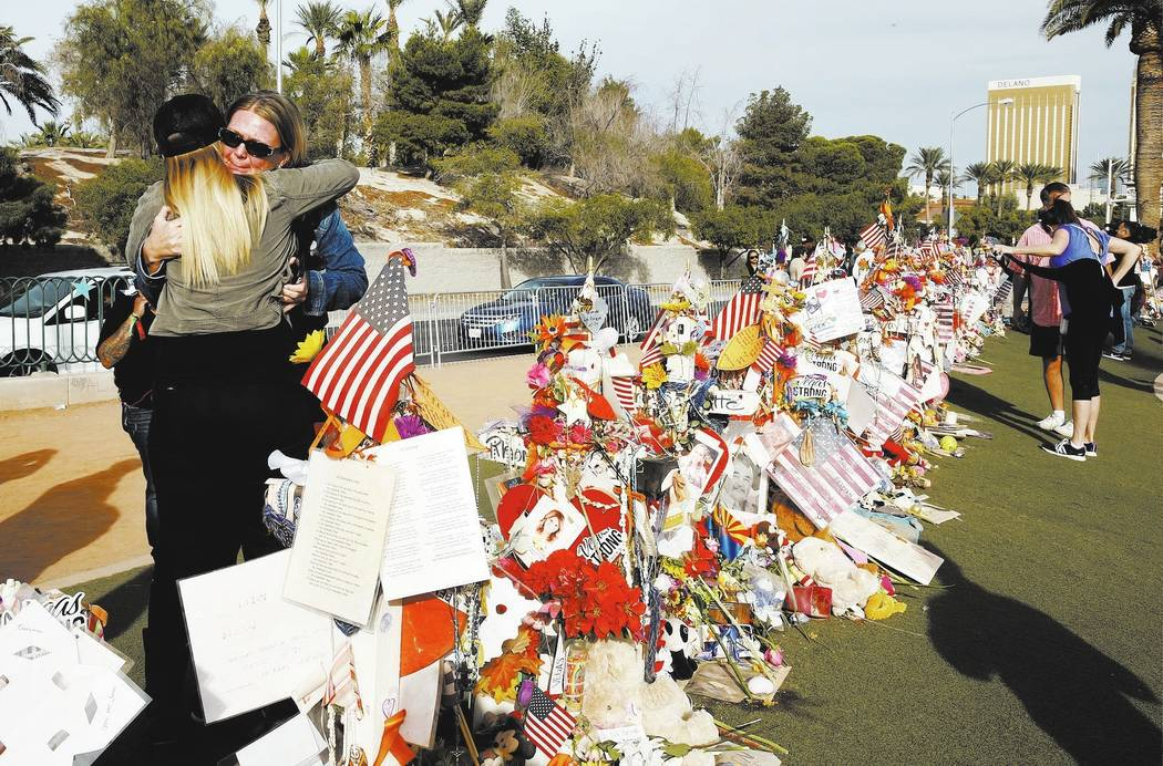 Las Vegas shooting survivors Kristy-Marie Hoff, left, and Shawna Bartlett hug each other as they visit a memorial for Route 91 Harvest shooting victims at the Welcome to Fabulous Las Vegas sign, S ...