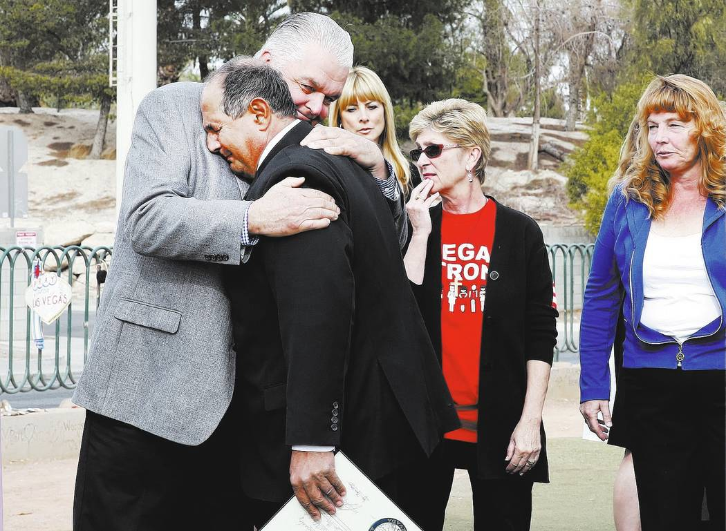"Clark County Commissioner Steve Sisolak, left, hugs Greg Zanis after declaring Sunday ""Greg Zanis Day"" at the Route 91 Harvest memorial at the Welcome to Fabulous Las Vegas sign Sund ..."