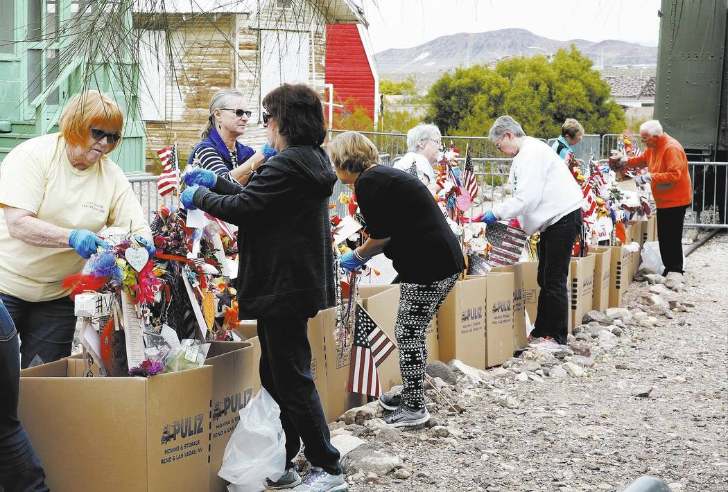 Volunteers, including Andrea Frazier, left, and Geraldine Ortiz, right, remove fragile artifacts from the crosses at the clark County Museum in Henderson Sunday, Nov. 12, 2017. Fifty eight crosses ...