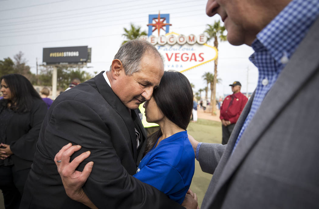 Tracy Shipp, center, sister of Route 91 victim Laura Shipp, is comforted by cross-maker Greg Zanis, left, and Clark County Commission Chairman Steve Sisolak following a cross-moving ceremony at a  ...