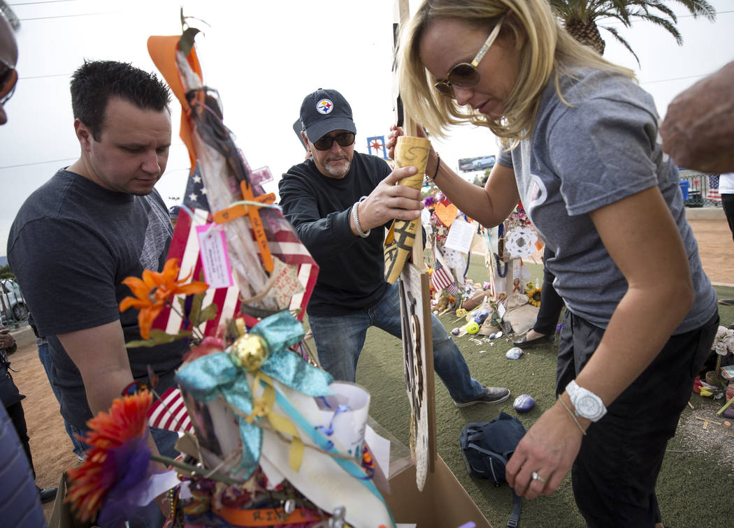 Chris Davis, center, and Mynda Smith, right, the father and sister of Route 91 shooting victim Neysa Tonks, gather items from Tonks' cross during a cross-moving ceremony at a memorial for the vict ...