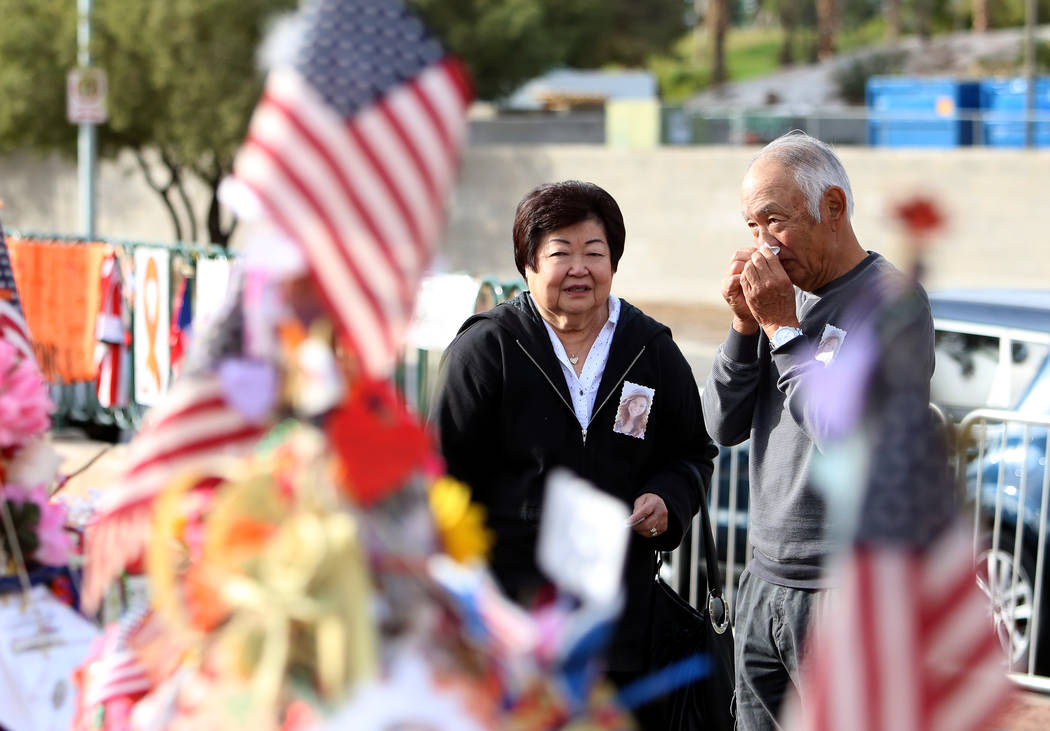 Haven Kimura, right, visits the cross of his daughter Nicole with his sister Violet at the Route 91 Harvest memorial at the Welcome to Fabulous Las Vegas sign Sunday, Nov. 12, 2017, in Las Vegas.  ...