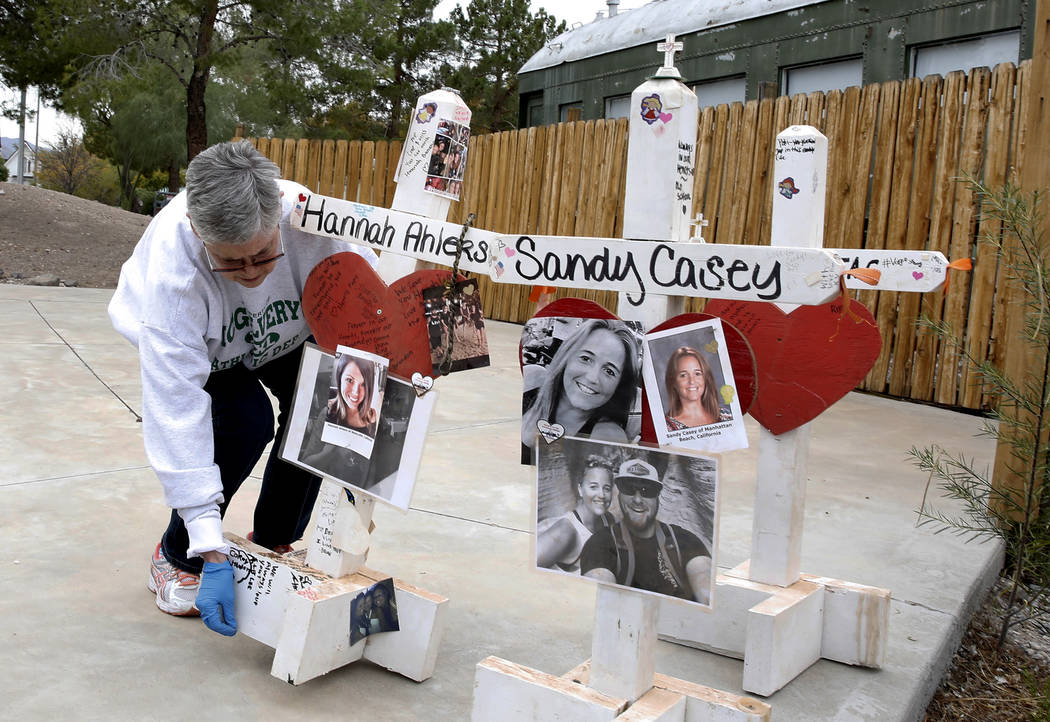 Jeanne Brady displays crosses on the amphitheater stage at the clark County Museum in Henderson Sunday, Nov. 12, 2017. Fifty eight crosses and items that were erected in honor of the Oct. 1 shooti ...