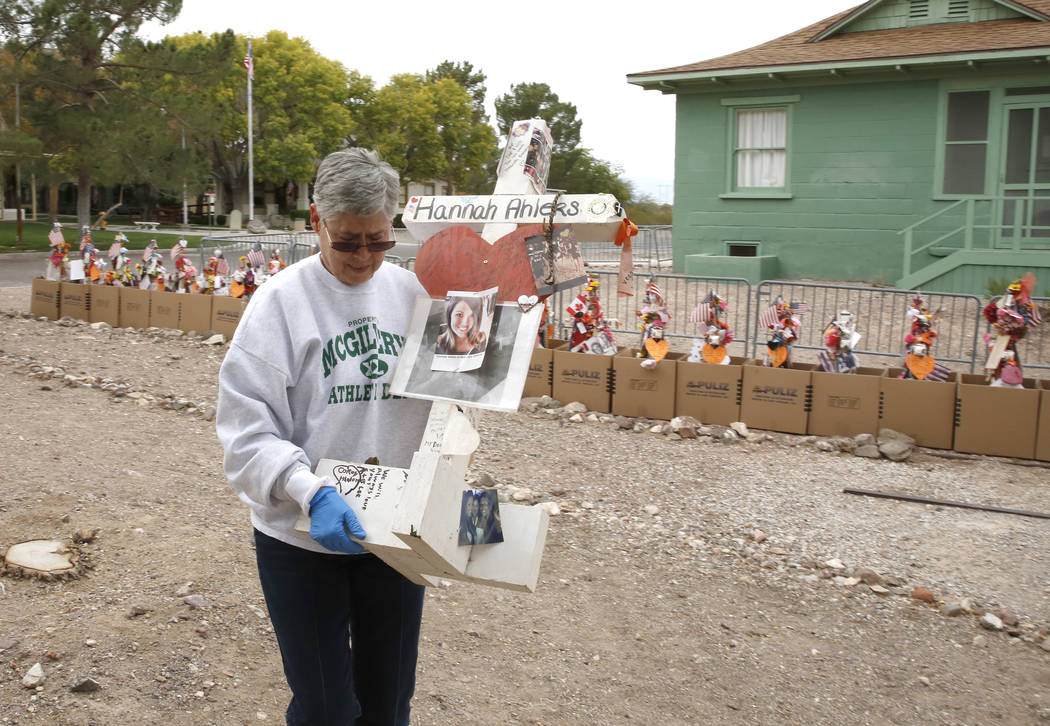 Jeanne Brady, a volunteer, carries a cross after removing fragile artifacts from the crosses at the clark County Museum in Henderson Sunday, Nov. 12, 2017. Fifty eight crosses and items that were  ...
