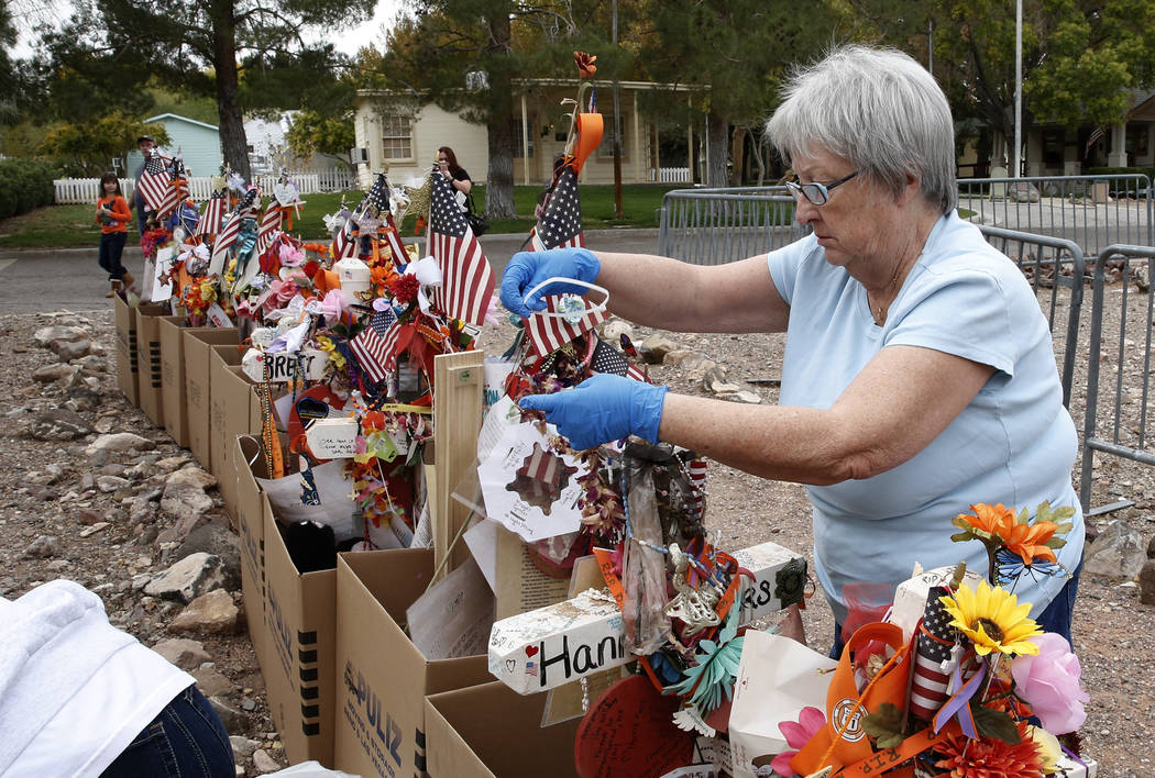 Janet Bremer, a volunteer, removes fragile artifacts from the crosses at the clark County Museum in Henderson Sunday, Nov. 12, 2017. Fifty eight crosses and items that were erected in honor of the ...