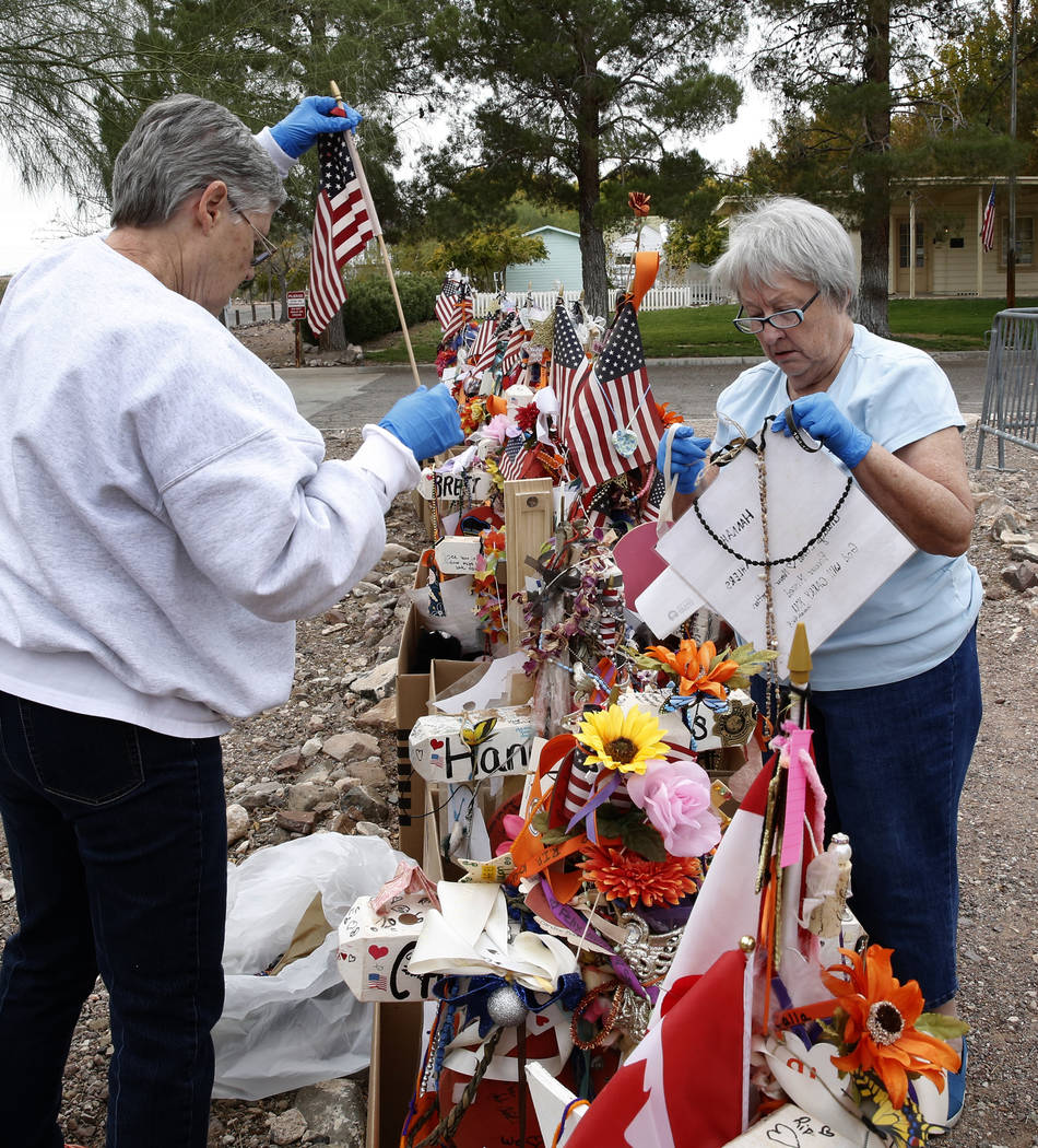 Jeanne Brady, left, and Janet Bremer, volunteers, remove fragile artifacts from the crosses at the clark County Museum in Henderson Sunday, Nov. 12, 2017. Fifty eight crosses and items that were e ...