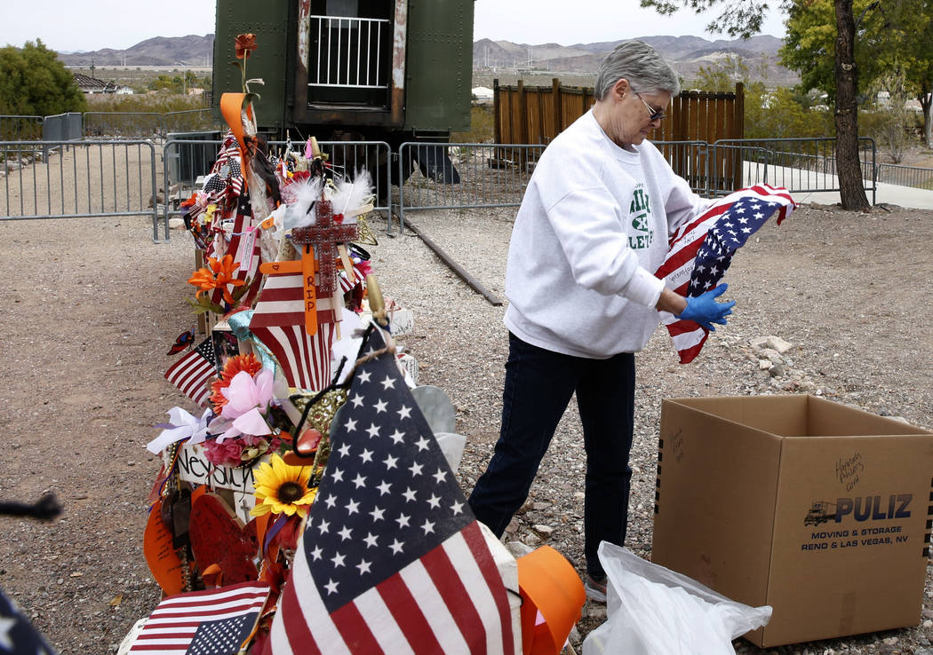 Jeanne Brady, a volunteer, folds an American Flag that was removed from the crosses at the clark County Museum in Henderson Sunday, Nov. 12, 2017. Fifty eight crosses and items that were erected i ...