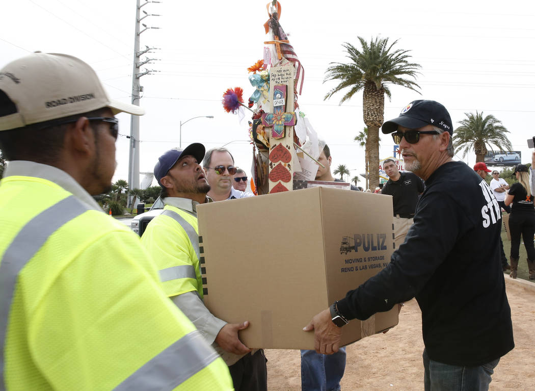 Chris Davis, right, helps Clark County employees carrying his Las Vegas shooting victim daughter Neysa Tonks' cross and items at the Welcome to Fabulous Las Vegas sign Sunday, Nov. 12, 2017. Fifty ...