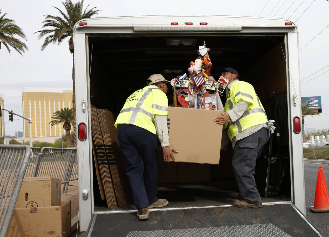 Clark County employees load crosses and items onto a truck at the Route 91 Harvest memorial at the Welcome to Fabulous Las Vegas sign Sunday, Nov. 12, 2017. Fifty eight crosses and items that were ...