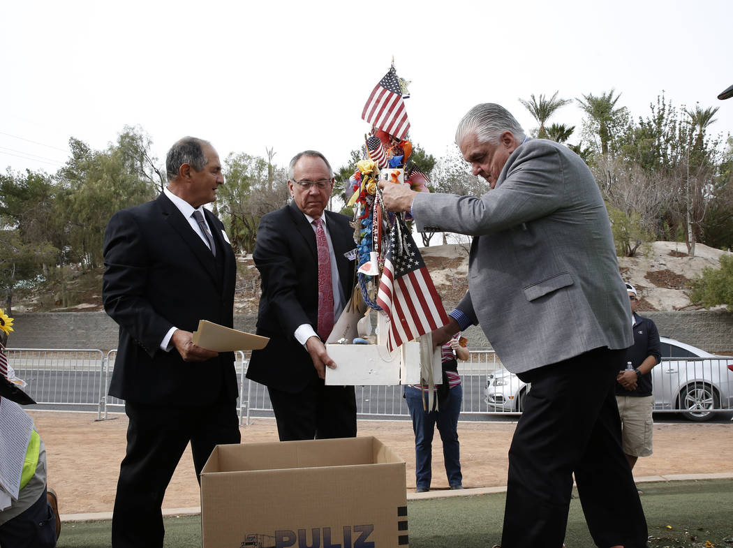 Clark County Commissioners, Jim Gibson, center, and Steve Sisolak, right, help removing crosses from the Route 91 Harvest memorial as Greg Zanis, who created the 58 crosses memorializing those who ...