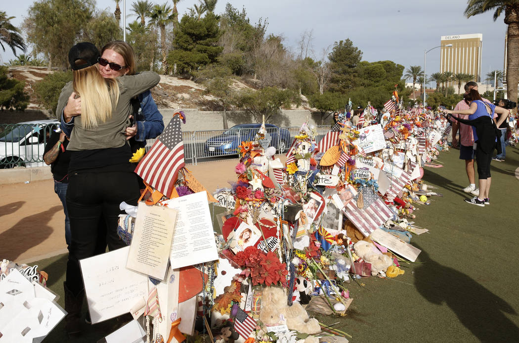 Las Vegas shooting survivors Kristy-Marie Hoff, left, and Shawna Bartlett hug each other as they visit a memorial for Route 91 Harvest shooting victims at the Welcome to Fabulous Las Vegas sign Su ...
