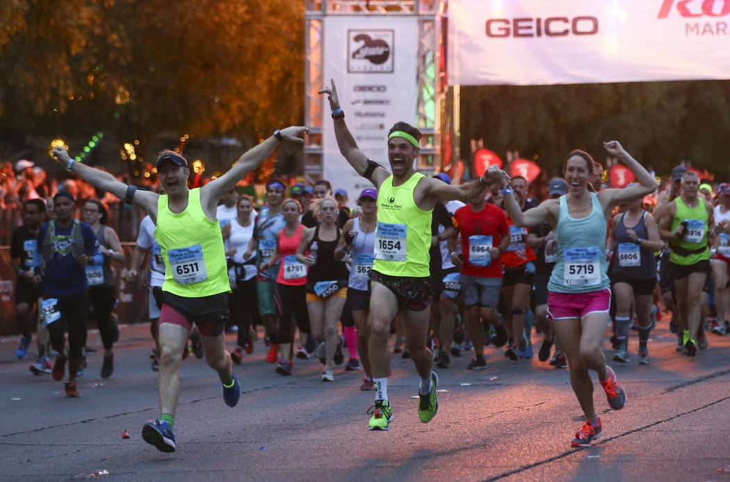 Participants, including, from left, Peter Smith, Scott Desbois, and Jen Desbois head out from the start line outside of the New York-New York at the beginning of the Rock 'n' Roll Marathon in Las  ...