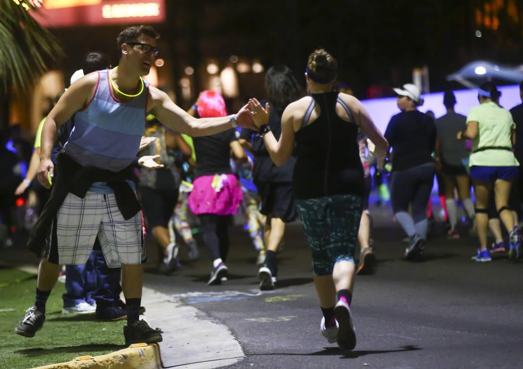 Aaron Hartman of Las Vegas, left, high-fives a race participant during the Rock 'n' Roll Marathon in Las Vegas on Sunday, Nov. 12, 2017. Chase Stevens Las Vegas Review-Journal @csstevensphoto