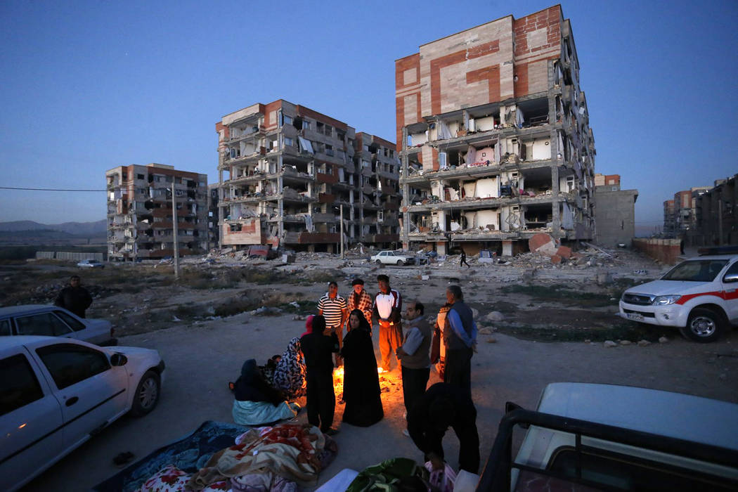 In this photo provided by the Iranian Students News Agency, ISNA, survivors of the earthquake warm themselves in front of destroyed buildings at the city of Sarpol-e-Zahab in western Iran, Monday, ...