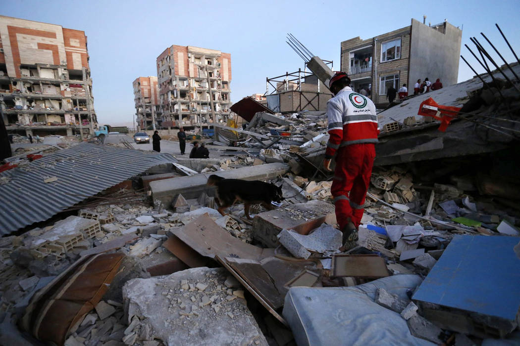 In this photo provided by the Iranian Students News Agency, ISNA, a rescue worker searches debris for survivors with his sniffing dog after an earthquake at the city of Sarpol-e-Zahab in western I ...
