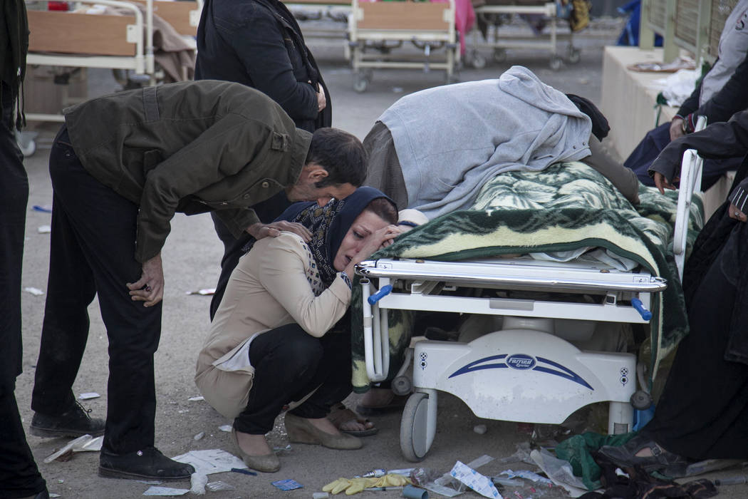 In this photo provided by Tasnim News Agency, relatives weep over the body of an earthquake victim,  in Sarpol-e-Zahab, western Iran, Monday, Nov. 13, 2017. Authorities reported that a powerful 7. ...