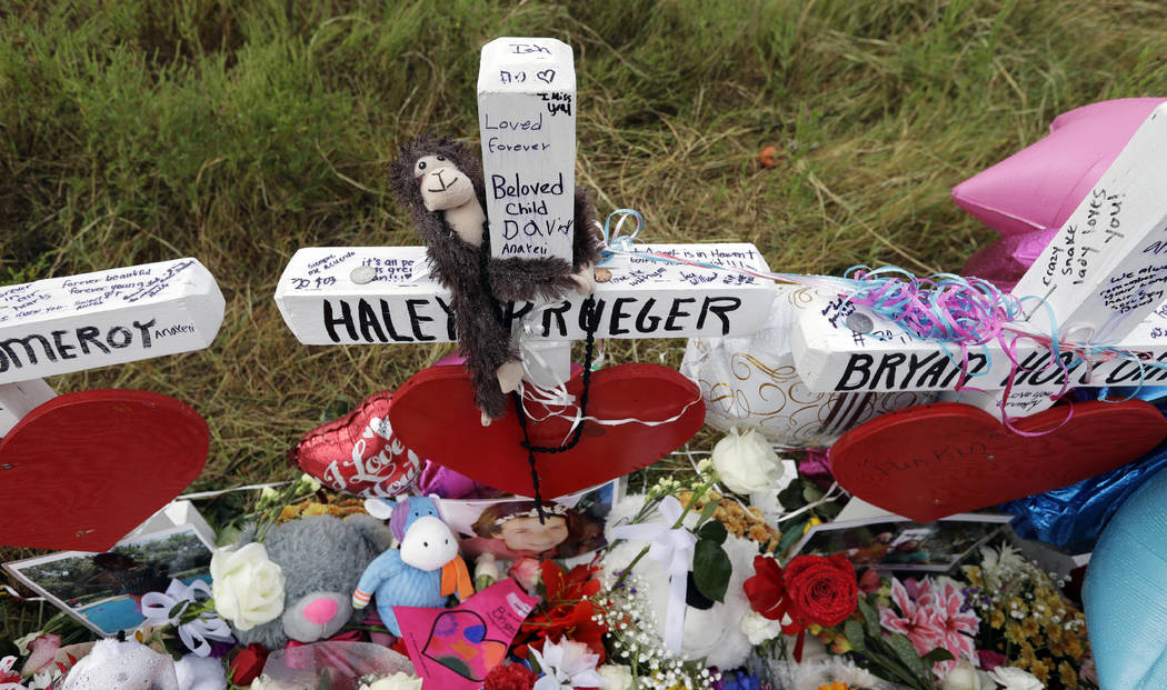Rain collects flowers, notes and items left at a makeshift memorial for the victims of the shooting at Sutherland Springs Baptist Church, Sunday, Nov. 12, 2017, in Sutherland Springs, Texas. A man ...
