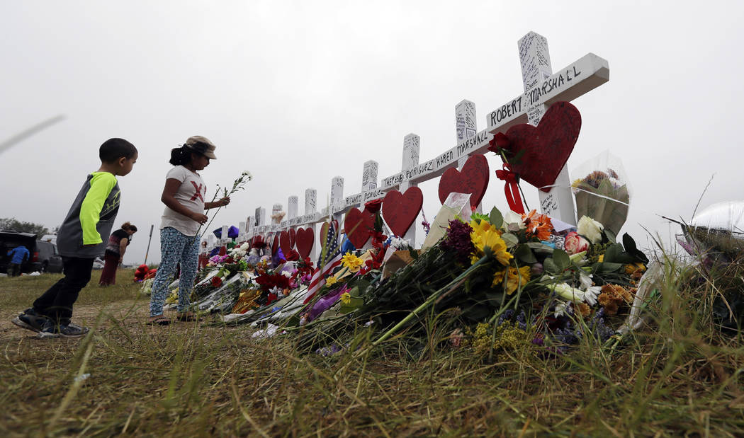 Alexander Osborn and Bella Araiza leave flowers at a makeshift memorial for the victims of the shooting at Sutherland Springs Baptist Church, Sunday, Nov. 12, 2017, in Sutherland Springs, Texas. A ...