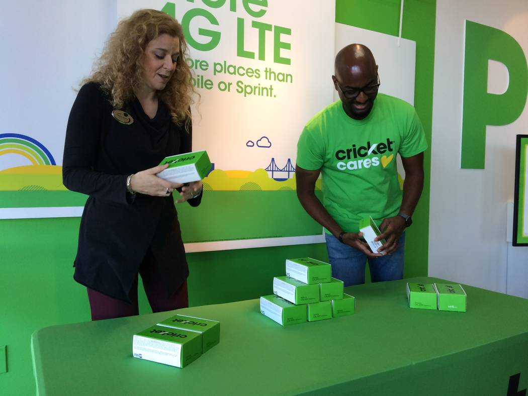 Daniele Dreitzer, executive director of The Rape Crisis Center, checks out one of the phones donated by Cricket Wireless Nov. 7, 2017, at the store on North Rainbow boulevard. Beside  her is Marlo ...