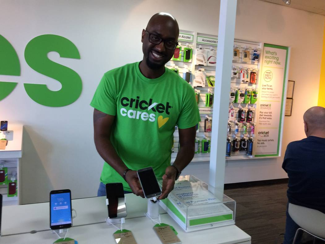 Marlon Young, territory sales manager for Cricket Wireless, shows the display model Nov. 7, 2017, for one of the 12 phones his company gave to the Rape Crisis Center. (Jan Hogan/View)