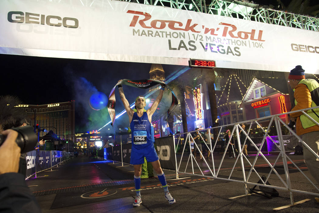Marathon winner Rubio Gilles holds the finish line banner aloft during the Rock 'n' Roll Las Vegas Marathon. (Sam Morris Las Vegas News Bureau)