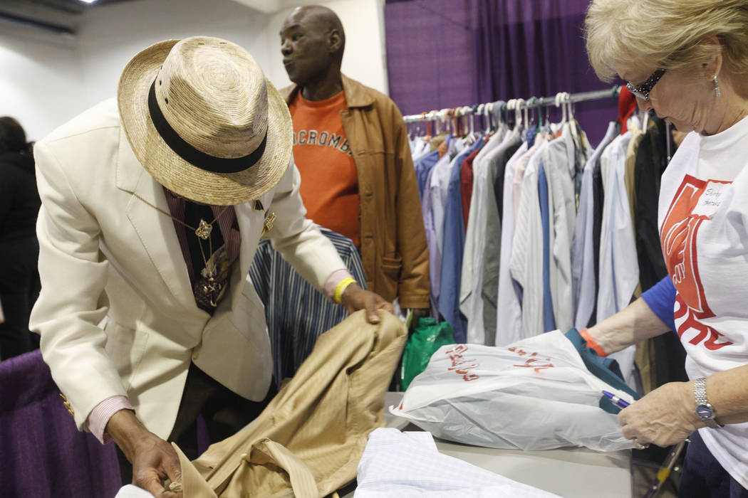 Kevin Washington lays out his new shirt and items with the help of volunteer Shirley Hartung at Project Homeless Connect, a service and resource fair for people who are homeless or at-risk at Cash ...