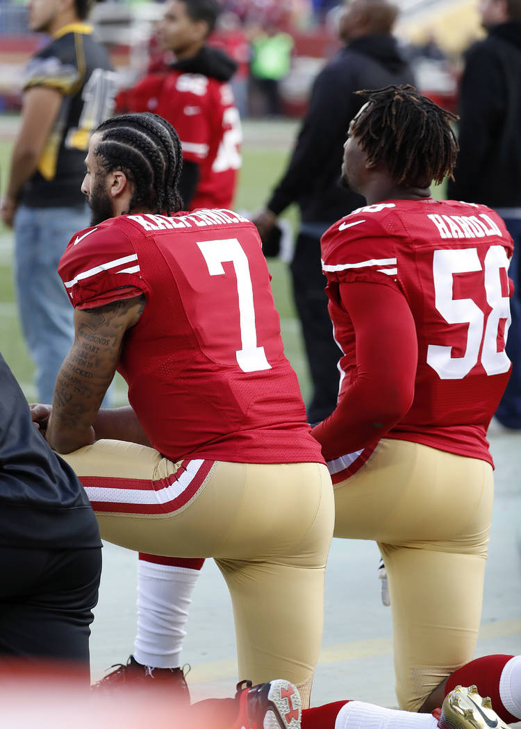 San Francisco 49ers quarterback Colin Kaepernick (7) and outside linebacker Eli Harold (58) kneel during the national anthem before an NFL football game against the Seattle Seahawks in Santa Clara ...