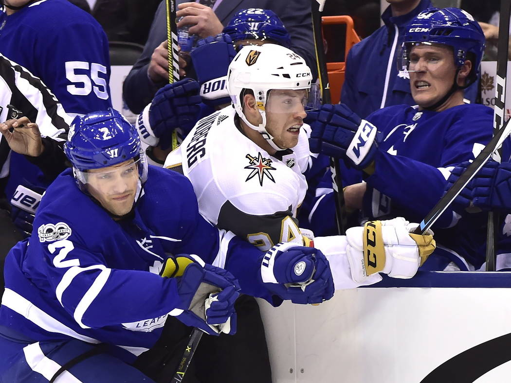 Toronto Maple Leafs defenseman Jake Gardiner (51) reacts on the bench as defenseman Ron Hainsey (2) checks Vegas Golden Knights center Oscar Lindberg (24) into the boards during the first period o ...