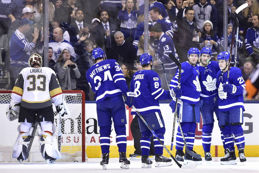 Vegas Golden Knights goalie Maxime Lagace (33) fishes the puck out of the net as Toronto Maple Leafs center Auston Matthews (34) defenseman Connor Carrick (8) defenseman Ron Hainsey (2) left wing  ...