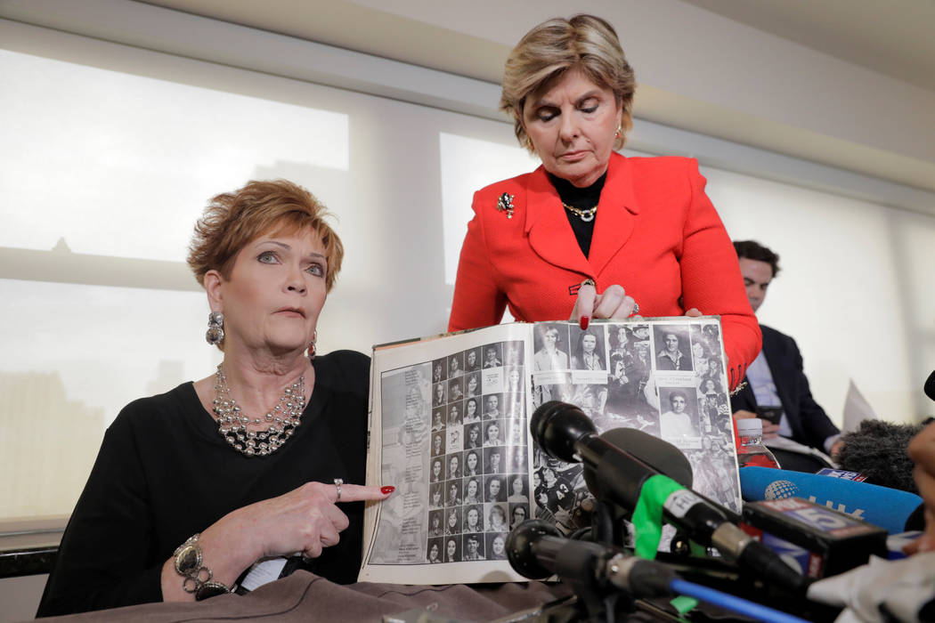 Beverly Nelson shows a school year book with attorney Gloria Allread during a news conference announcing new allegations of sexual misconduct against Alabama Republican congressional candidate Roy ...