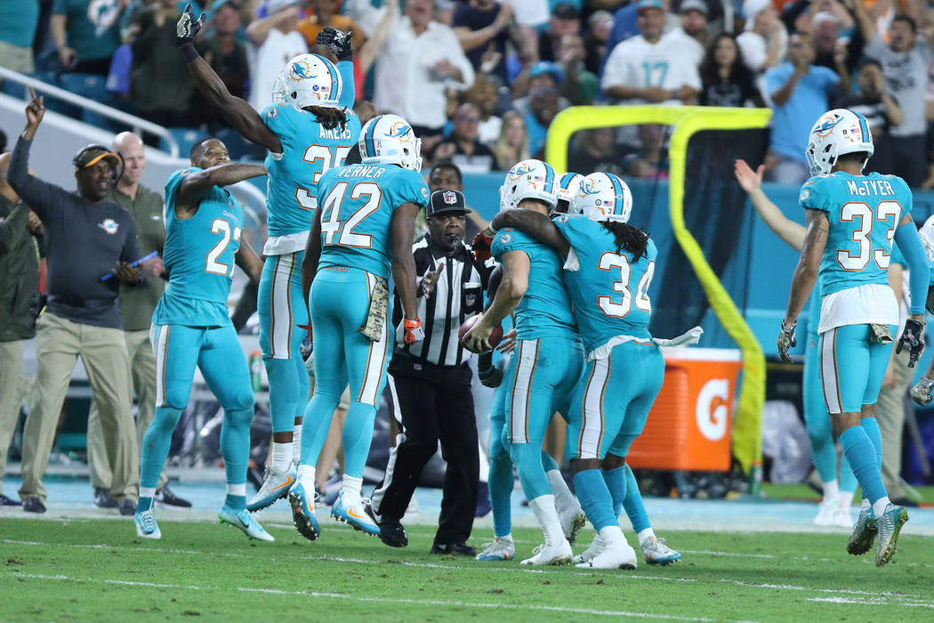 Miami Dolphins kicker Cody Parkey (1) holds the football and celebrates with teammates after recovering his own onside kick during the first half of the NFL game against the Oakland Raiders in Mia ...