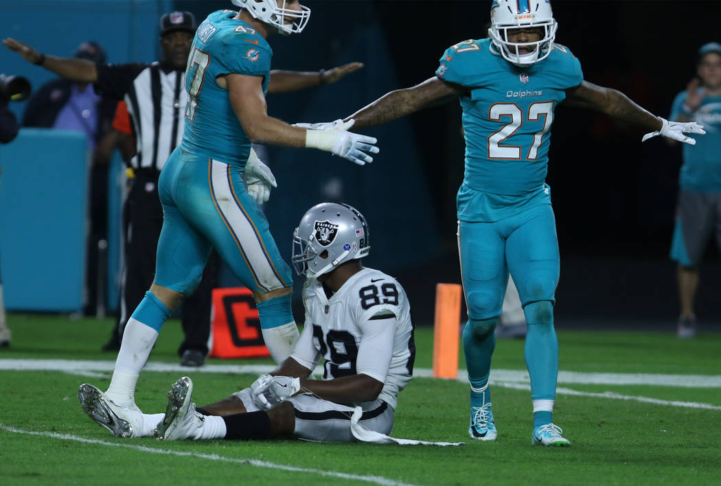 Oakland Raiders wide receiver Amari Cooper (89) rests on the field after an incomplete pass defended by Miami Dolphins middle linebacker Kiko Alonso (47) and safety Maurice Smith (27) during the f ...