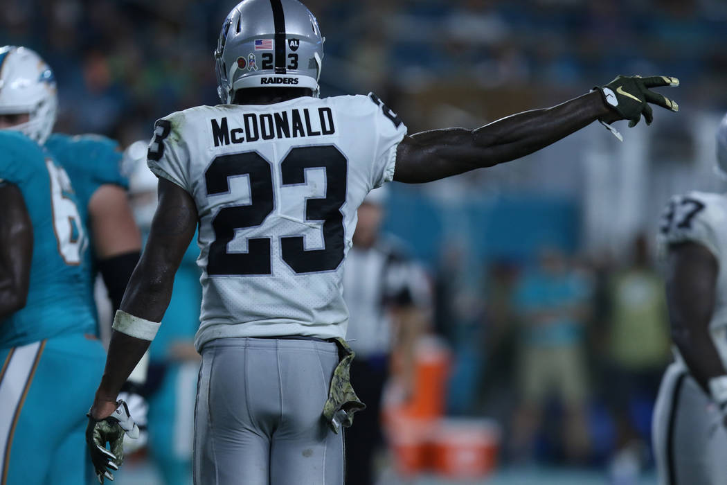 Oakland Raiders cornerback Dexter McDonald (23) signals the ball is theirs after a turnover by Miami Dolphins running back Kenyan Drake (32) during the first half of the NFL game in Miami Gardens, ...