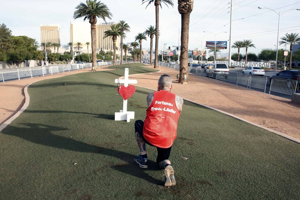 Stephan Klein of Germany, who came to run the Rock 'n' Roll Las Vegas Marathon, takes a picture of a white cross that was left at the Route 91 Harvest memorial site at the Welcome to Fabulous Las  ...