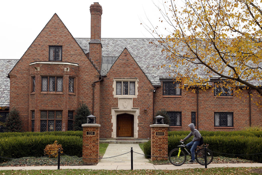 A bicyclist rides past Pennsylvania State University's shuttered Beta Theta Pi fraternity house Thursday, Nov. 9, 2017, in State College, Pa. Centre County, Pa., District Attorney Stacy Parks Mill ...
