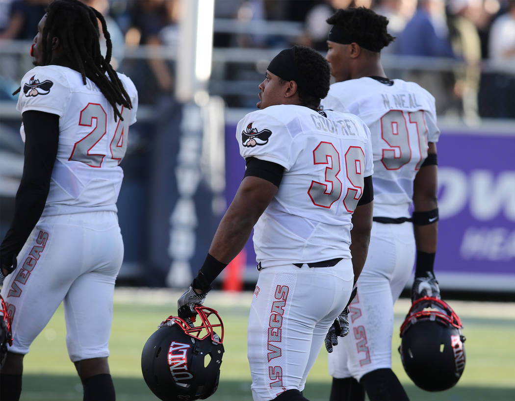 UNLV Rebels defensive back Robert Jackson (24), linebacker Daniel Godfrey (39) and defensive lineman Nate Neal (91) leave the field after taking a loss to the Nevada Wolf Pack in Reno, Saturday, N ...