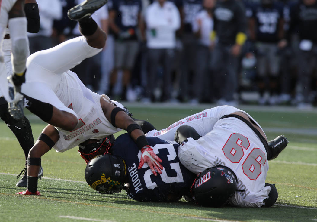 UNLV Rebels defensive lineman Mike Hughes Jr. (99) and defensive back Jericho Flowers (7) tackle Nevada Wolf Pack running back Kelton Moore (23) during the second half of their game in Reno, Satur ...